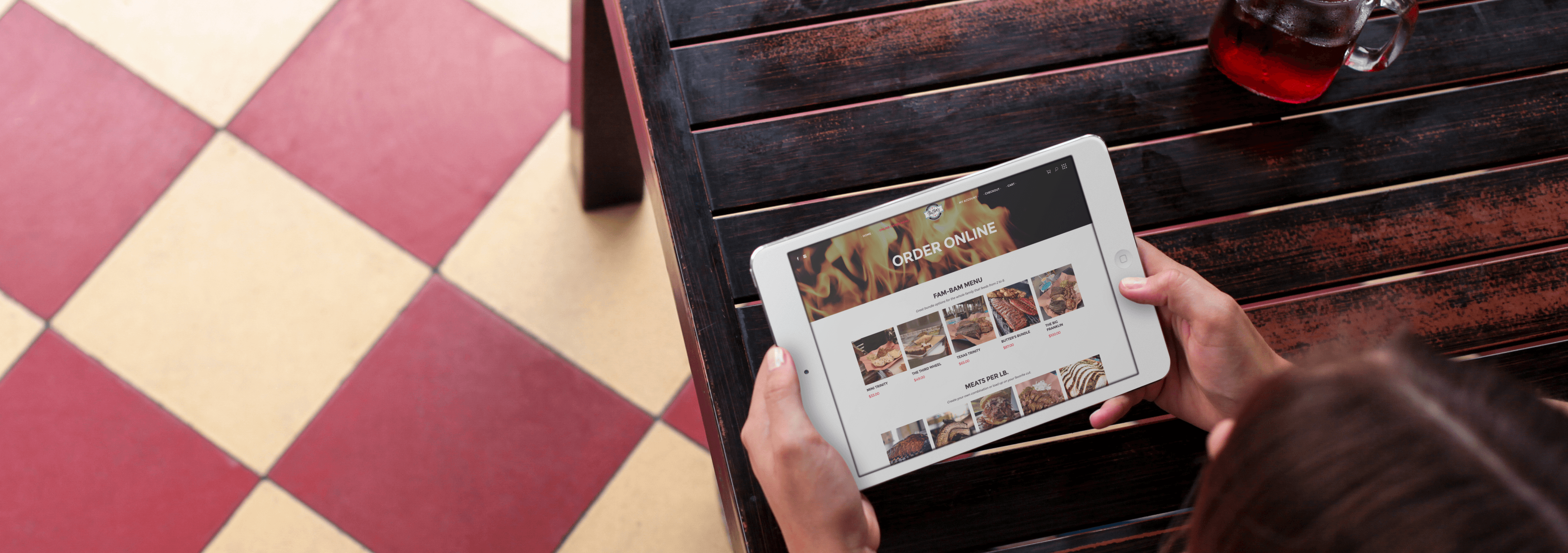 tablet mockup of a woman using an ipad mini at a restaurant - Butter's Barbecue